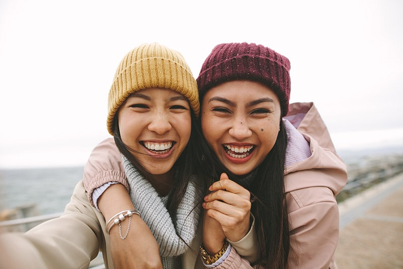 Two friends happily take a selfie together after visiting the dentist.