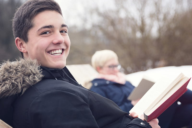 A young man smiles after reviewing his dental insurance plan.